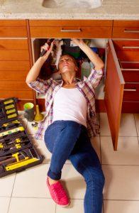 Jeune femme en train de réparer sa plomberie sous l'évier de la cuisine