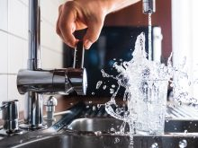 Personne en train d'activer un robinet de cuisine pour se servir une verre d'eau